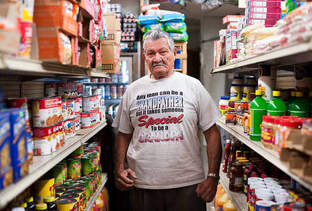 Bronx resident, Santos, poses in a bodega (small grocery store) in Hunts Point, Bronx. Photo: Chris Arnade.