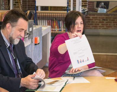 Rachel Donegan, JD, describes the demographic profile of Upton/Druid Heights neighborhood as SSW Dean Richard P. Barth, PhD, MSW, reviews Promise Heights documents. Photo: UMB School of Social Work