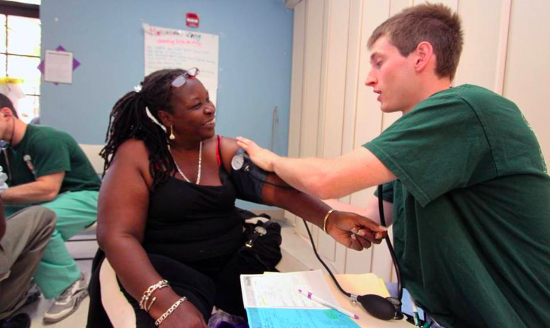 Yvette Phillips, of Miami, has her blood pressure taken by University of Miami medical student Daniel Nelson at an event in Liberty City last year that offered free services to residents. Photo: Theo Karantsalis.