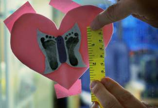 Dr. Theresa Grover, medical director of Children's Hospital Colorado's neonatal intensive care unit, measures a footprint of an infant on Nov. 16, 2015. who was born three months premature at the hospital. Photo: Rocky Mountain PBS News.
