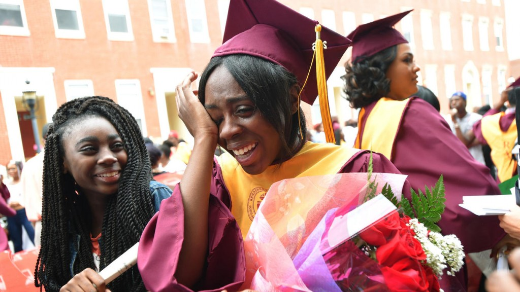 Kashawna Mattocks wipes tears from her eyes after her graduation from the Renaissance Academy. Her sister, Charney Mattocks, is at her side.