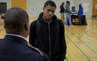 Khalil talks to a military recruiter at a school career fair.