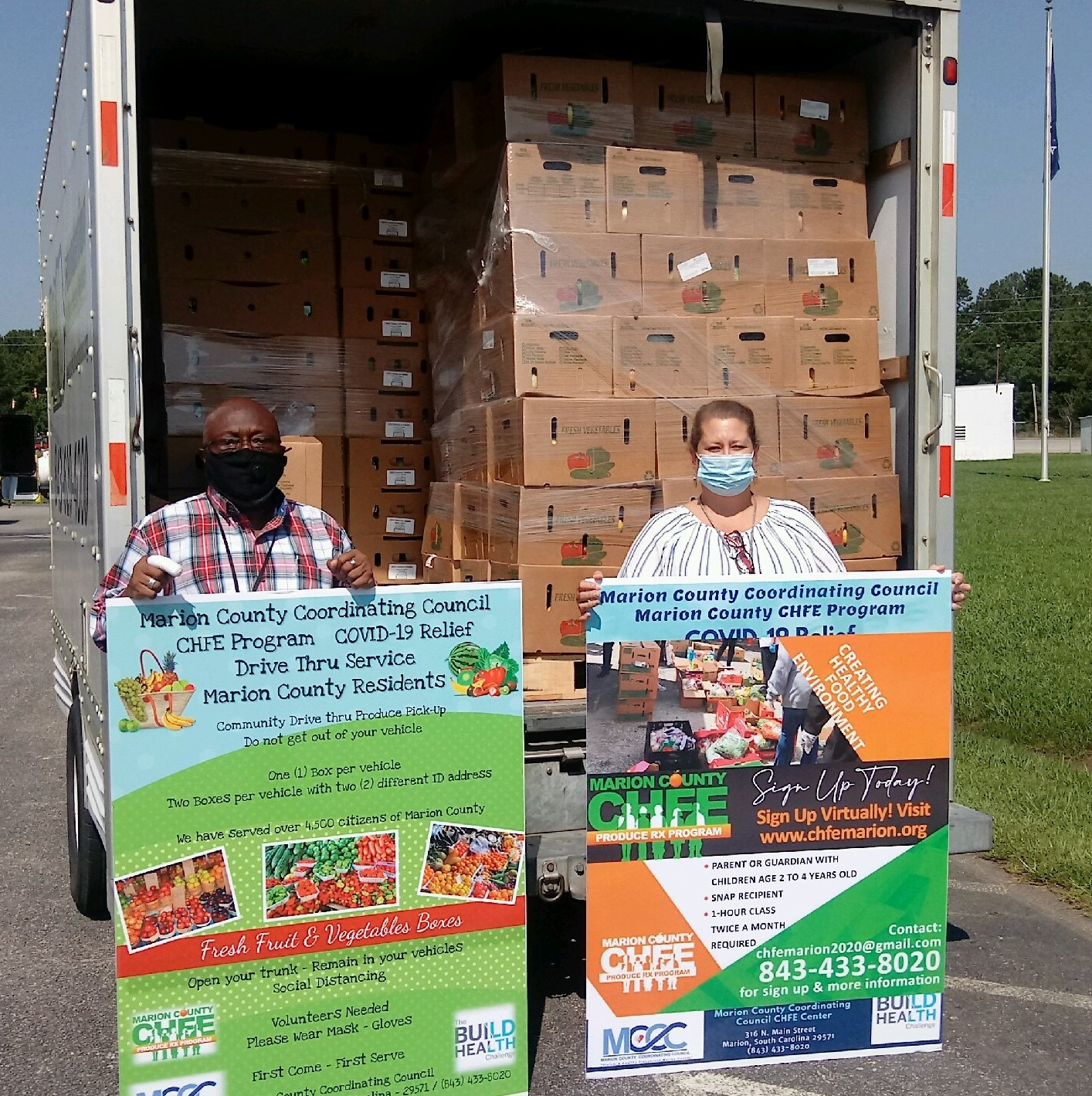 Staff pose in front of a truck stocked with food for distribution.